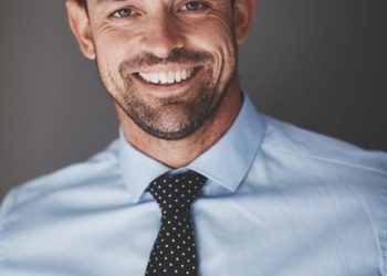 Confident young businessman smiling while wearing a shirt and tie and standing against a gray background